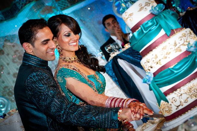 beautiful Indian bride and groom, cut wedding cake, wedding mehndi